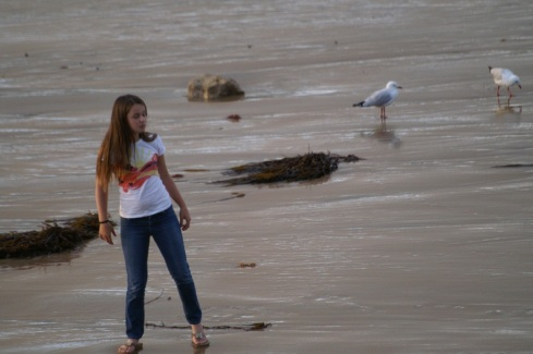 Girl and gull on beach near Port Campbell on the Great Ocean Drive